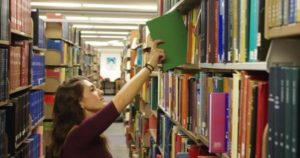 Student pulling a book off the shelves