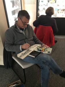 A member of Urban Sketchers Delaware drawing in his notebook.