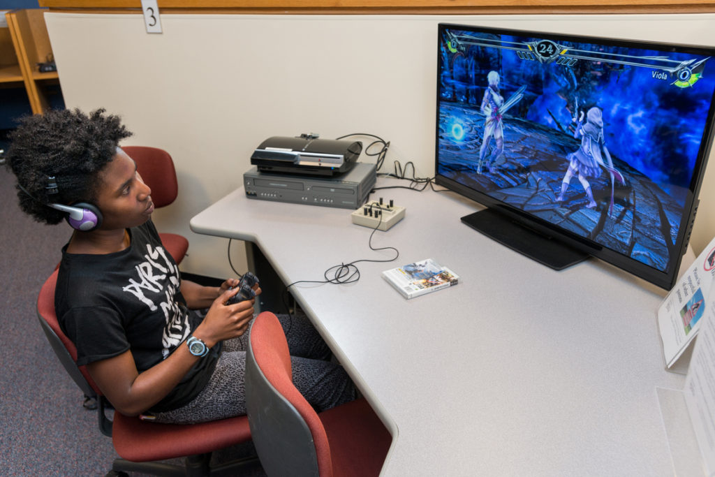 A UD student plays Soul Calibur on a gaming station in the Film and Video Collection.