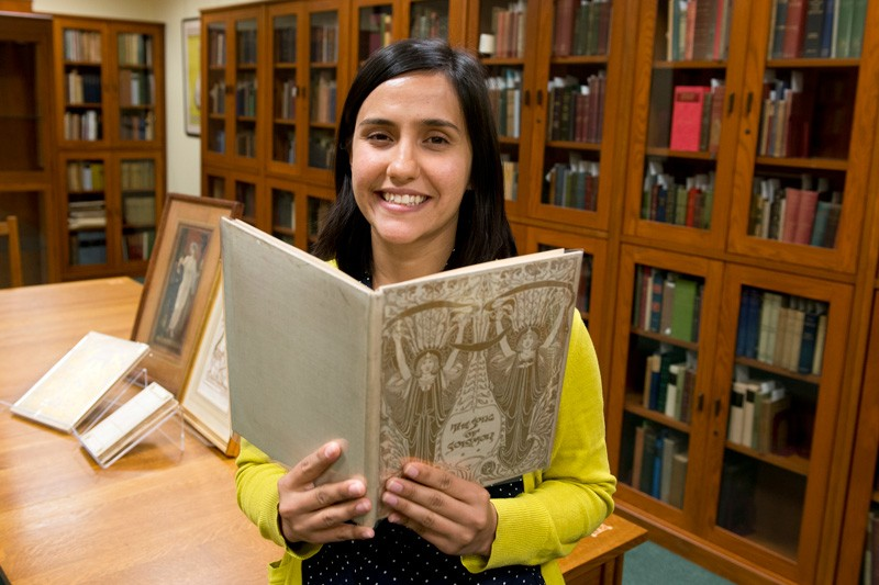 Tara Contractor, a doctoral candidate from Yale University's History of Art Department, holds a book from the University of Delaware's Mark Samuels Lasner Collection. As recipient of this year's Amy P. Goldman Fellowship in Pre-Raphaelite Studies, Contractor has been using the University's collections as well as materials from the Delaware Art Museum for research during her fellowship residency.