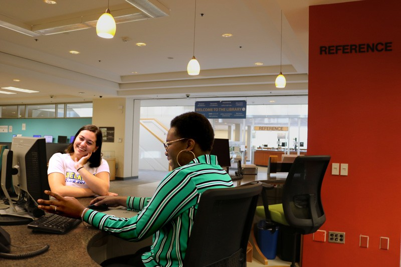 A student speaks with a Librarian at the Morris Library Reference Desk