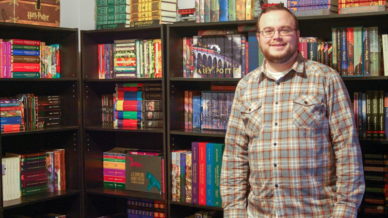 Sean McAllister stands in front of bookshelves displaying his Harry Potter collection.
