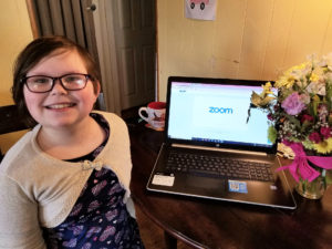 Image of Abby standing next to a laptop with Zoom open