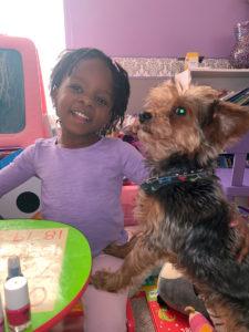 Image of three-year-old Maya and her dog.