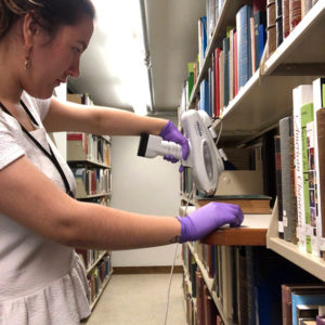 A young woman standing along a shelf of books, with a piece of equipment pressed against a book to read its elemental analysis.