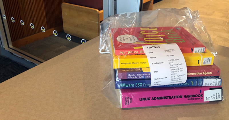 A stack of books in a clear bag sitting on a table.