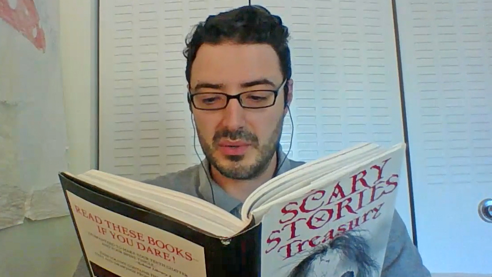 """A man looking down as he reads a book """"Scary Stories Treasury"""""""