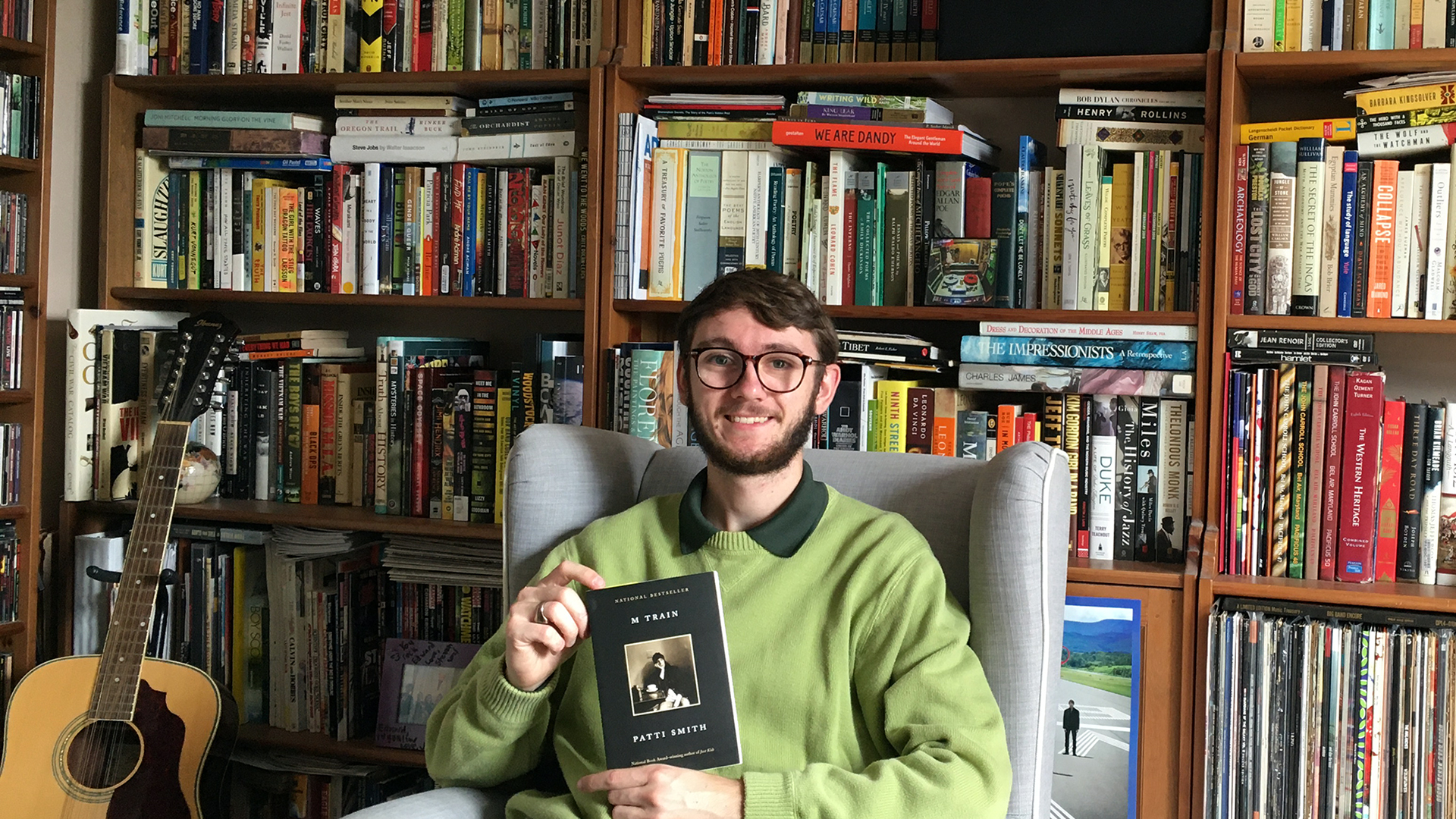 A young man in a green sweater holding a book in his hands as he sits in a chair. He is sitting in front of a massive wall of bookshelves, filled with books stored in a variety of directions.