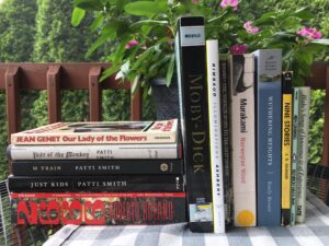 A stack of books next to a row of standing books on a table outside.