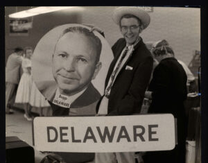 """A black and white photo of a young man in a suit jacket and a funny hat, standing with a giant circular photo of a politican and a sign that reads """"Delaware"""""""