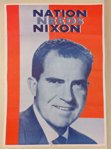 """An oversized poster that says """"Nation Needs Nixon"""" with a print of Richard Nixon on it overtop a red and white background."""