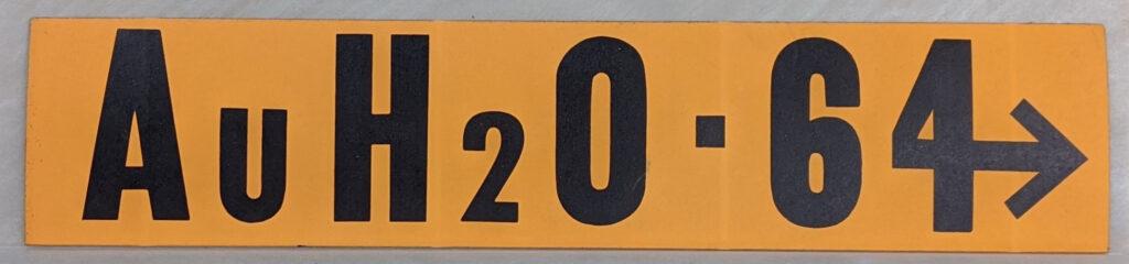 "A goldish yellow bumper sticker that reads ""AuH20 64"""