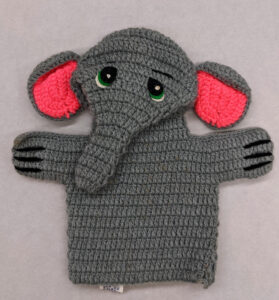 A hand puppet of a gray elephant with the insides of his ears pink.