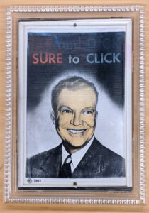"""A holographic print in a frame. The current view shows Richard Nixon smiling, with the words """"Sure to Click"""" above his head. The full, unshown text of the print is """"Ike and Dick Sure to Click"""""""