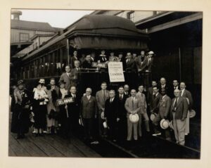"""A black and white photo of men and women standing in front of a stopped train. Some are holding up signs that say """"Delaware."""""""