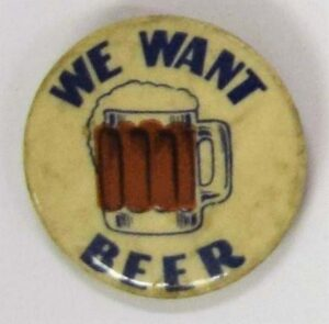 """A weathered button that says """"We Want Beer"""" with a glass mug of beer in the middle."""