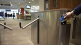 The entrance turnstiles to Morris Library opening as someone taps their UD ONEcard to get in.